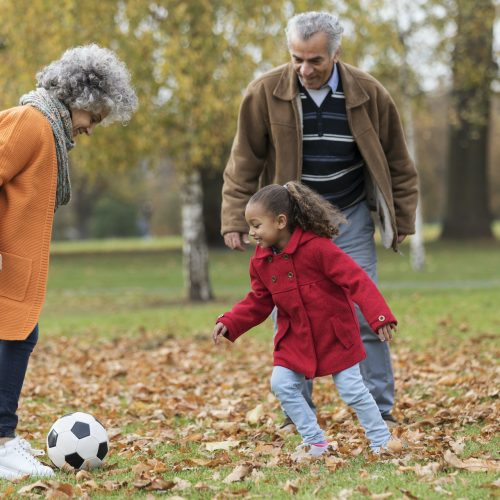 Grandparents playing soccer with granddaughter in autumn park