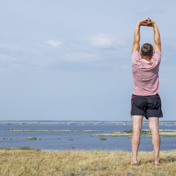 A middle-aged man doing exercises in the fresh air by the lake